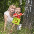 Stock Photo: Young mother and infant daughter relaxing in park