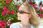 Cute girl wearing sunglasses outdoor on flower background — Stock Photo