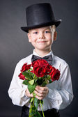 Handsome boy wearing classic suit with flowers in hands — Stock Photo