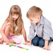 Stock Photo: Two playing kids with alphabet isolated on white background