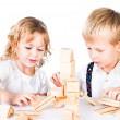 Two kids playing with wooden blocks indoor on white background — Stock Photo