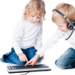 Two children playing with computer on floor isolated on white background — Stock Photo