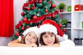 Sisters in red santa hat — Photo