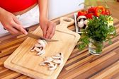 Woman cutting mushrooms — Stock Photo
