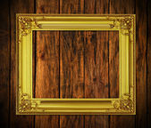 Old antique gold frame on wood background — 图库照片
