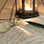 un viejo libro abierto por la luz de las velas — Foto de Stock
