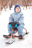 Happy little boy for a walk in a winter park, sledging at sleig — Stock Photo