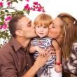 Parents kissing daughter - Stock Photo