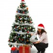Stock Photo: Opening Christmas presents near decorated tree