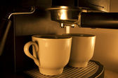 Coffee maker pouring hot espresso coffee in two cups. Take your break! — Zdjęcie stockowe