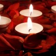 Red petal of the roses and small candles in water — Stock Photo #7160315