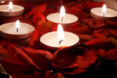 Red petal of the roses and small candles in water — Stok fotoğraf