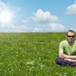 Young man on green meadow — Stock Photo