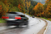 Black car on autumn road — Stockfoto