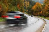 Czarny samochód na drodze jesień — Zdjęcie stockowe