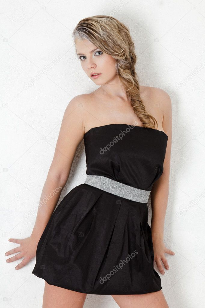 Attractive young blonde fashion model in black mini dress against white wall — Stock Photo #7940474
