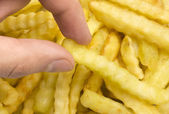 Grabbing Crinkle French Fry — Stock Photo