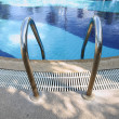 Foto Stock: Swimming pool ladder handrail.