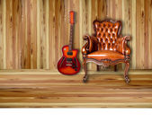 Uxury leather armchair and sunburst electric guitar on wood background — Stock Photo