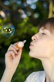 Young girl inflates soap bubbles — Stock Photo