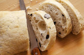 Sliced loaf of baguette bread and knife sitting on cutting board. — Stock Photo