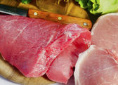 Meat and knife on board — Stock Photo