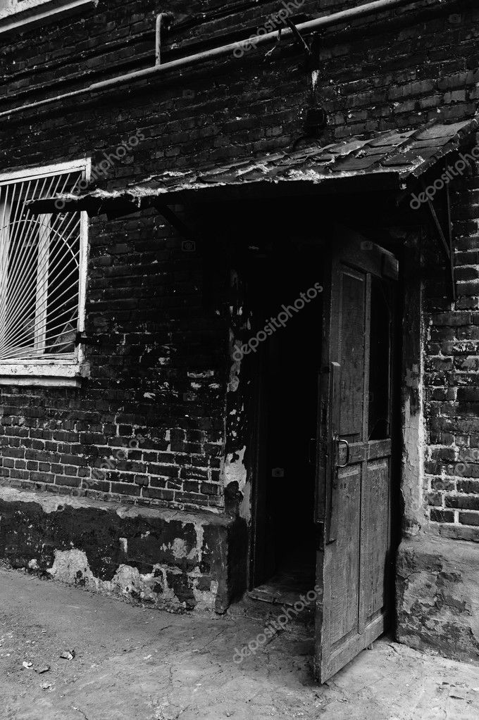Open old door leading into a dark entrance. Black and white photo in low key — Stock Photo #6867721