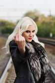 "Seductive young girl showing middle finger (""fuck off"" gesture) — Stock Photo"