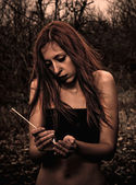 Beautiful young sad girl with match in hands — Foto de Stock