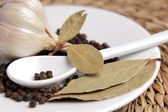 Bay list, garlic and black pepper peas in a white saucer — Stock Photo