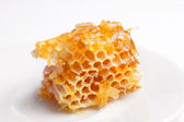 Honey comb on a white saucer. — Stock Photo