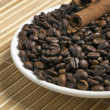Stock Photo: Coffee beans with tubes of cinnamon on white saucer