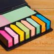 Multicolored post it note block in black leather case — Stock Photo