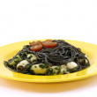 A yellow plate with black pasta and squid — Stock Photo