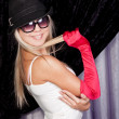 Stylish blond model in white shirt with a red glove — Stock Photo