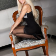 Beautiful blond woman in sexy black dress in vintage chair — Stock Photo