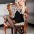 Sexy blond girl in sensual black dress in vintage chair — Stock Photo
