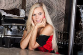 Smiling pretty blond girl at bar table — Stock Photo