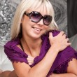 Beautiful blond girl in stylish sun glasses and violet scarf — Stock Photo