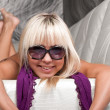 Young smiling blond girl in stylish sun glasses and violet scarf — Stock Photo