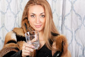 Gorgeous brunette girl in a fur coat with an empty glass — Stockfoto