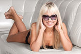 Attractive blond girl in stylish sun glasses and dark lingerie — Stock Photo