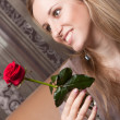 Smiling blond girl with a red rose — Stock Photo