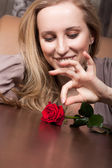 Sensual blond woman with a red rose — Стоковое фото