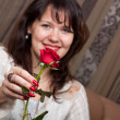 Sensual brunette woman with a red rose — Stock Photo