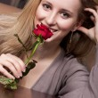 Lovely young blond girl holding a red rose — Stock Photo