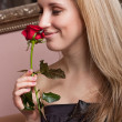 Joyful blond girl with a red rose — Stock Photo