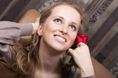 Beautiful smiling blond girl with a red rose — Foto de Stock
