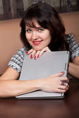 Lovely young brunette girl with a laptop — Stock Photo