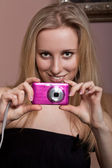Smiling young girl with a photo camera — Stock Photo